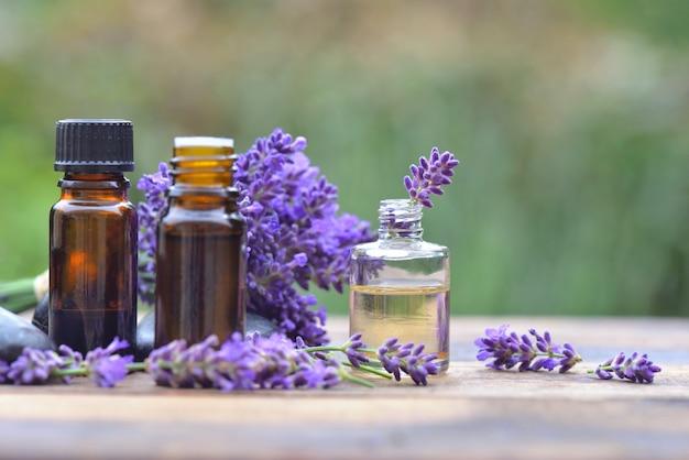Бутылки эфирного масла среди цветов лаванды, расположенных на деревянном столе в саду