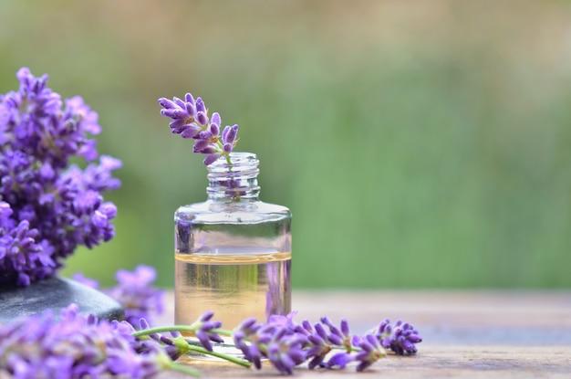 Закройте на фиолетовый цветок лаванды в бутылке эфирного масла на столе в саду