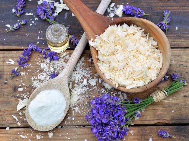 Ложка, полная хлопьев мыла с эфирным маслом и букетом цветов лаванды и бикарбоната натрия на деревянном фоне