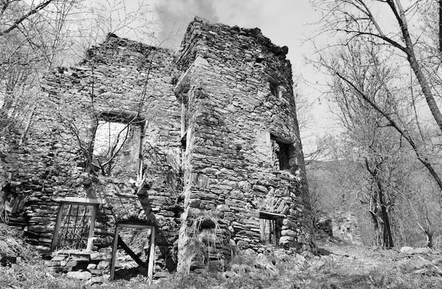 Белые и черные руины каменного дома заброшенной деревни в лесу