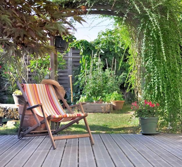 Шезлонг на деревянной террасе в саду