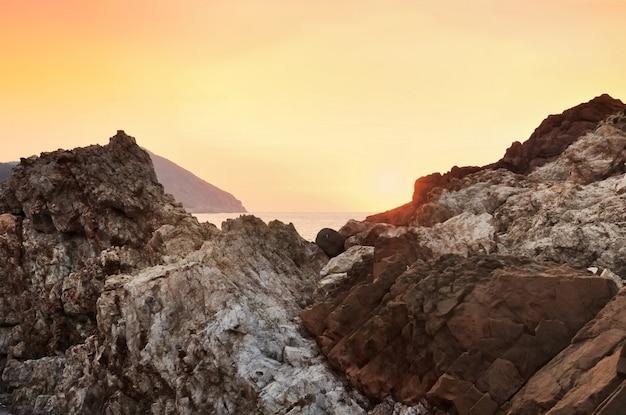 Красивый закат на оранжевых скалах залива на корсике