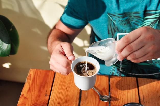 カフェの男が朝にクリームを一杯のコーヒーに注ぐ