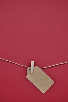 紙のラベルは、洗濯ばさみで赤のロープに取り付けられています。