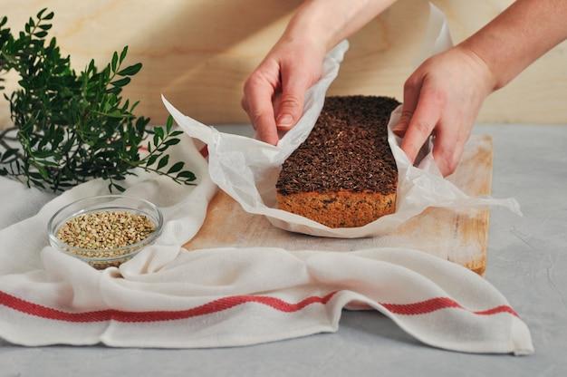 亜麻の種子、木製の背景に女性の手の中のヒマワリと緑のそばのパンに自家製ビーガンのパン。健康で適切な栄養