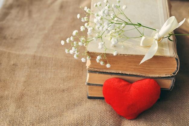 バレンタインデーの白い花、黄ばんだ古書、黄麻布の上の赤い豪華な心のヴィンテージの素朴な愛のカード。閉じる