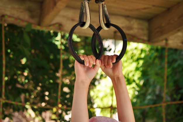 遊び場で金属リングにつかまって子供の手