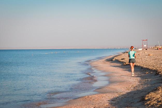 浜辺の少女が海に沿って朝のジョギングをする