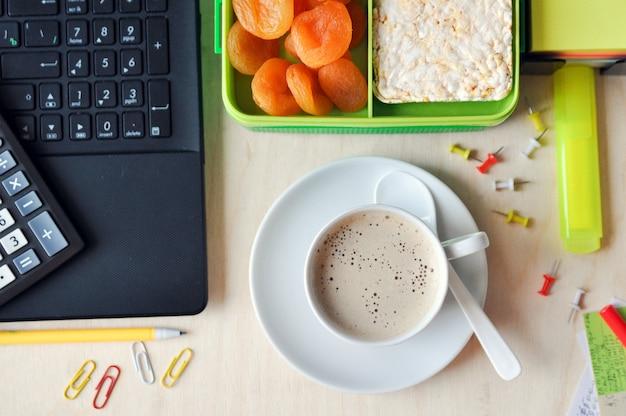 オフィスや学校での食べ物。デスクトップ上の健康食品と一杯のコーヒーのお弁当。上面図。