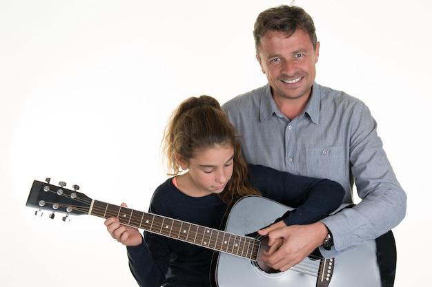 Прекрасная молодая девушка получает уроки игры на гитаре с человеком