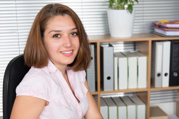 Успешная деловая женщина улыбается и работает в офисе