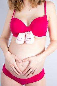 Беременная счастливая женщина, держа в руках детская обувь. мама ждет ребенка