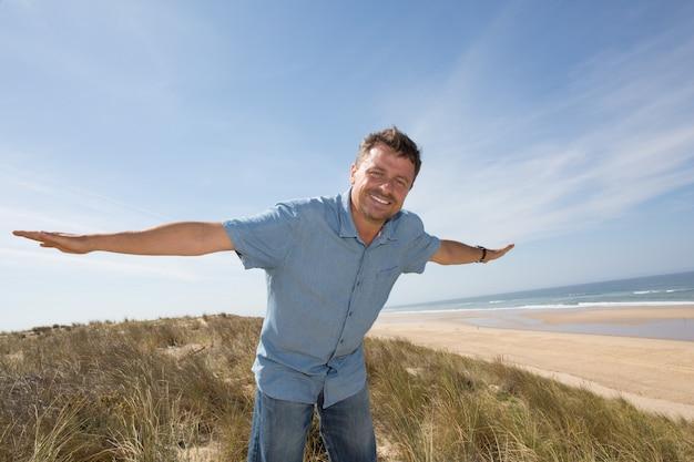 Человек смотрит вдаль руками против моря