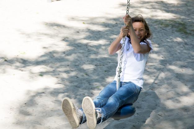 陽気な女の子は子供のために公園でジップラインを作る