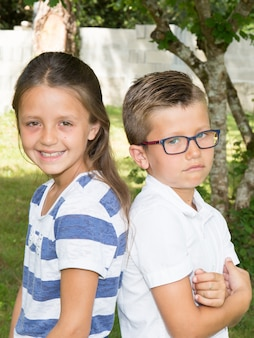 兄と妹が外に座っています。眼鏡の悲しい少年