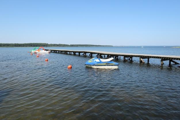 湖の木製ポンツーンの横にあるジェットスキーとペダルボート