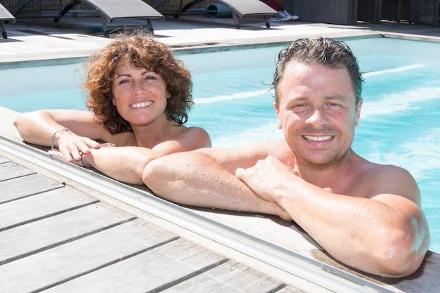休日のホテルのスイミングプールで一緒にリラックスして、夏休みを楽しんでいる成熟した愛情のあるカップルの側の肖像
