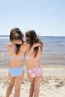 Две привлекательные девушки в бикини на пляже. лучшие друзья веселятся, летние каникулы отдых стиль жизни счастливые женщины красота