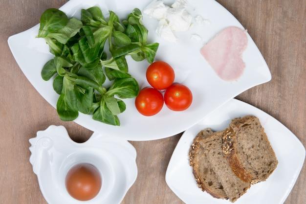 Салат из помидоров и ветчины в форме сердца на деревянный стол