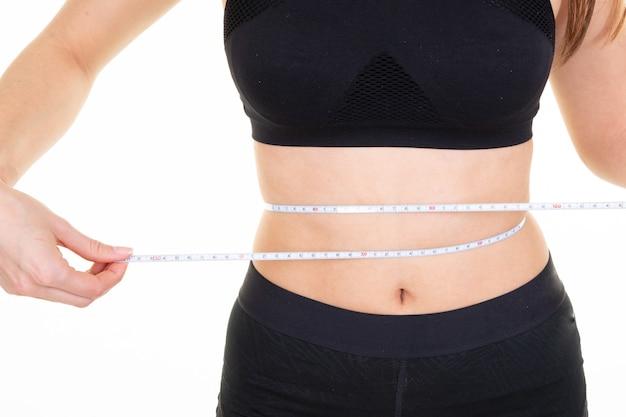 測定テープでスリムな若い女性の腰にフィット