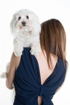 白い犬を抱いた若い女性の背面図。