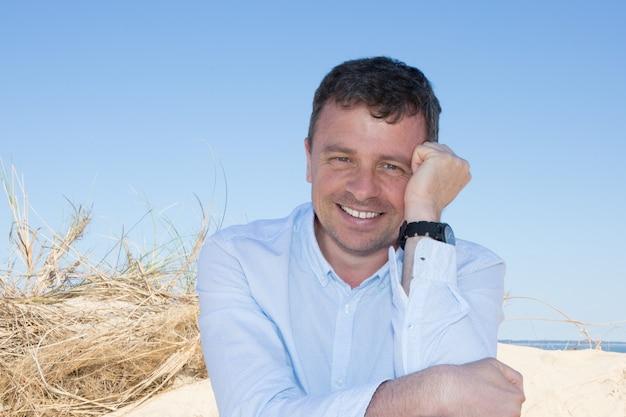 海のそばに座って幸せと笑顔の男