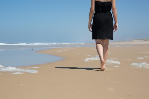 白人女性は美しい海岸に沿って歩く