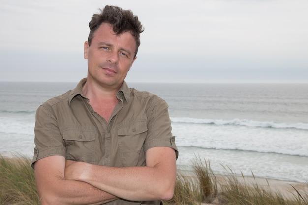 Красивый мужчина стоял на пляже и задумчиво смотрит вдаль