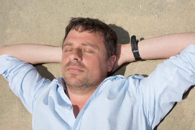 Мужчина на пляже отдыхает на песке