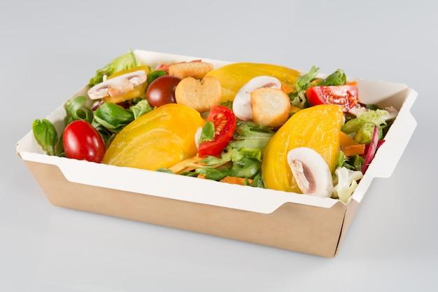 Большой салат в картонной тарелке быстрого питания забирают