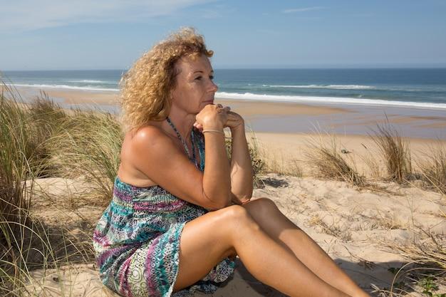 Блондинка и серьезная зрелая женщина на пляже