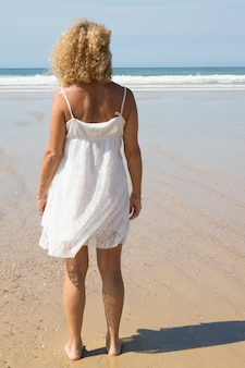 一人でビーチで美しいブロンドの女の子