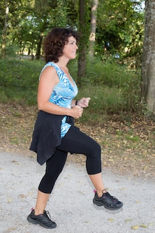 Брюнетка женщина средних лет растяжение ноги в парке
