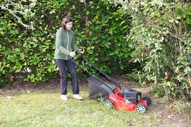 女性は彼女の庭の木の間の芝生を刈る