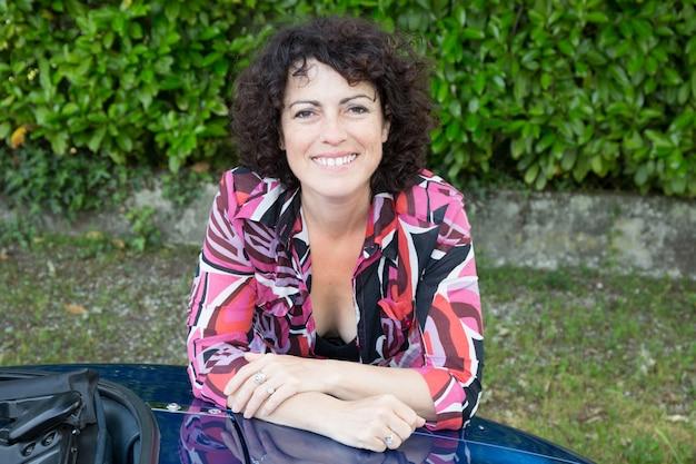 Красивая женщина, опираясь на капот своей машины