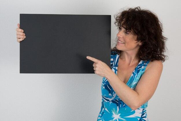 空白の黒いプラカードを指している素敵な女性