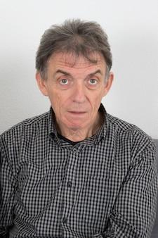 灰色のハヌカの装飾に分離された驚いた年配の男性の肖像画