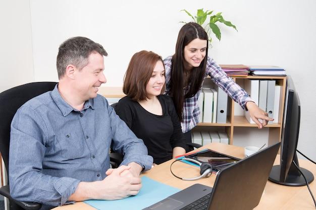 一緒に机に座って作業し、通信する若いビジネス人々のグループ