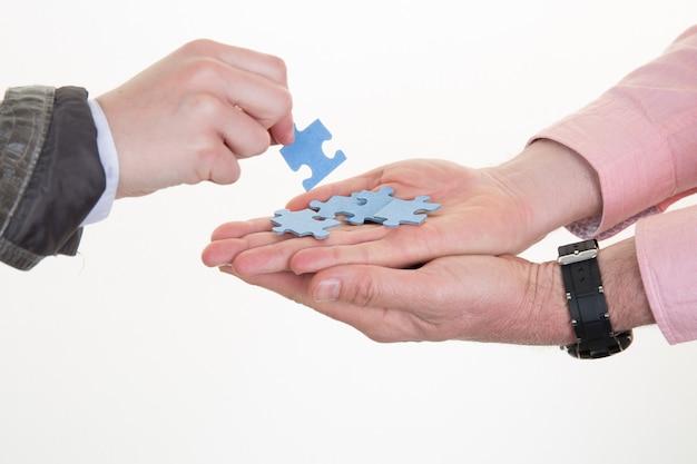 ビジネスマンやビジネスウーマンは、オフィスでパズルのピースを与えます