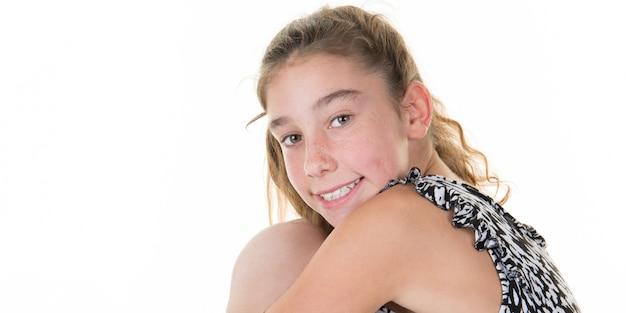 巻き毛を持つ若い女の子が床の笑顔の上に座る