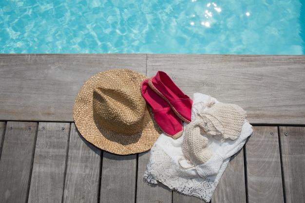 かわいいピンクの靴とプールサイドの夏の帽子