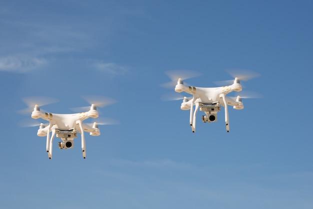 Изображение двух дронов под голубым небом