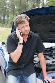 故障車屋外のボンネットの下を見てヘルプサービスのための電話の男