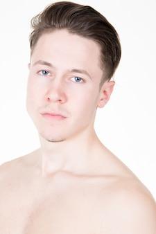 Портрет без рубашки мускулистый мужчина стоит на белом фоне, глядя в камеру
