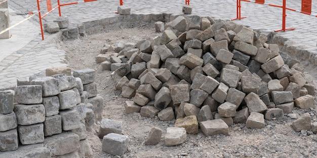 石畳の舗装での作業のために準備された花崗岩の加工片の山
