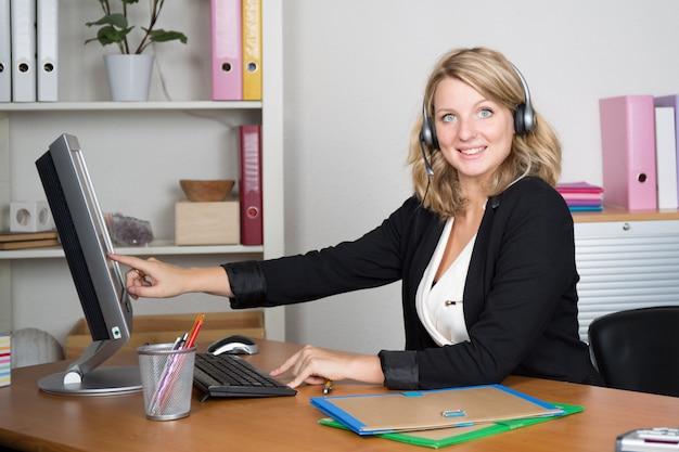 明るいオフィスでコンピューターに取り組んでいる自信を持って金髪コールセンターエージェント