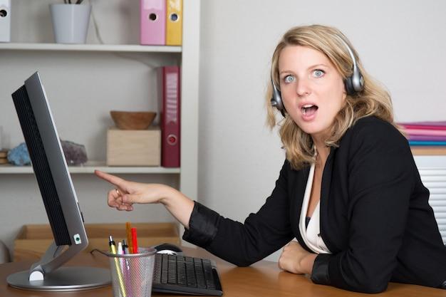驚いている彼女のコンピューターを探している金髪の若い女性