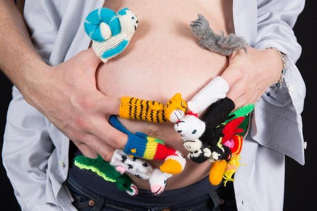 Шерстяные фигурки на пальцах женщины с ее руками на животе беременной
