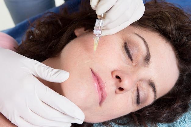 女性の顔にヒアルロン酸注射を行う美容師の女性の手を閉じる