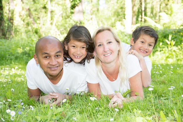Молодая семья смешанной расы, лежа и отдыхая в зеленом парке в прекрасный летний день
